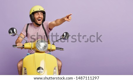 Happy delighted man points into distance, notices something cool and awesome, wears protective helmet, drives motorbike, has long trip or journey, isolated on purple background. Driver on moped #1487111297