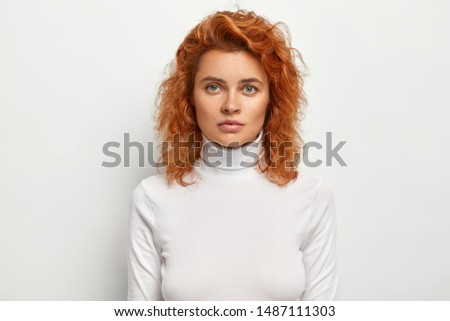 Headshot of serious good looking female looks seriously at camera, has confident face expression, has ginger wavy hair, wears casual polo neck, isolated on white background. People and beauty concept #1487111303