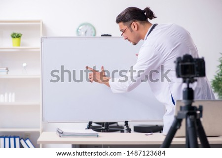 Young male doctor recording video for his blog  #1487123684