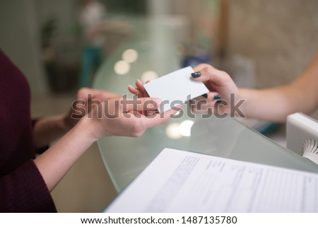 Giving name card. Close up of helpful receptionist giving name card of dentist for client