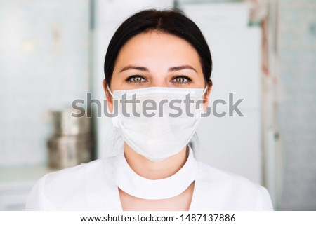 Close up portrait of young woman doctor with medical mask. Nurse looking at camera on hospital background. #1487137886