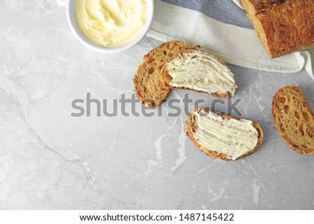 Tasty bread with butter served for breakfast on grey marble table, top view. Space for text #1487145422