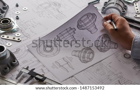 Engineer technician designing drawings mechanicalparts engineering Engine manufacturing factory Industry Industrial work project blueprints measuring bearings caliper tools Royalty-Free Stock Photo #1487153492