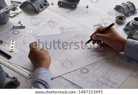 Engineer technician designing drawings mechanical parts engineering Engine manufacturing factory Industry Industrial work project blueprints measuring bearings caliper tools #1487153495
