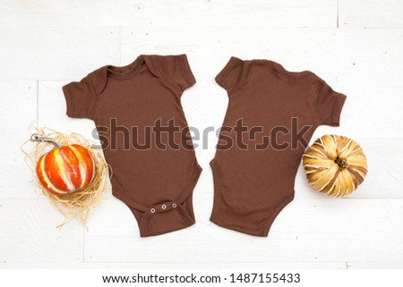 Two blank brown baby bodysuits on white wood background with two pumpkins, front and back thanksgiving/fall bodysuit mockup #1487155433