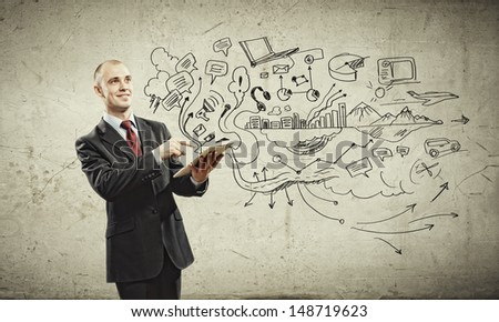 Image of young businessman holding ipad against sketch background