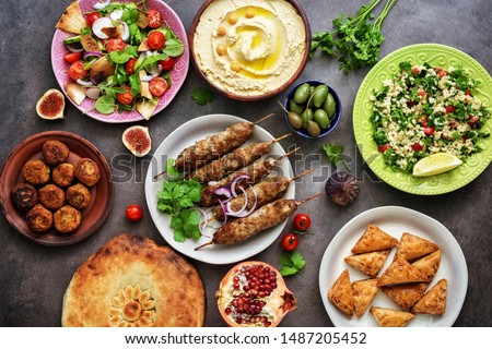 Assorted variety of Arabic and Middle Eastern food on a dark rustic background. Hummus,tabbouleh salad, salad Fattoush,pita,meat kebab,falafel,baklava. Set of Arabian dishes.Top view #1487205452