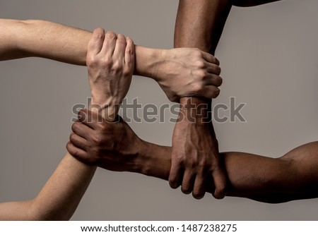 Races united against discrimination and racism. Black African American and Caucasian hands holding together in world unity and racial love and understanding. Tolerance and cooperation concept. #1487238275