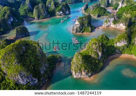 Aerial view Vung Vieng floating fishing village and rock island, Halong Bay, Vietnam, Southeast Asia. UNESCO World Heritage Site. Junk boat cruise to Ha Long Bay. Famous destination of Vietnam Royalty-Free Stock Photo #1487244119