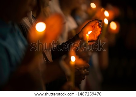 The yellow candle light is protected from the hand by the wind and in the picture there is a niose.