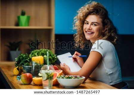 Nutritionist working in office. Doctor writing diet plan on table and using vegetables. Sport trainer. Lifestyle. #1487265497