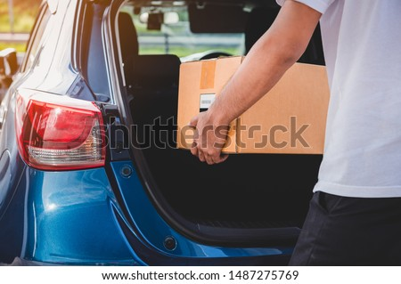 Delivery man is delivering cardboard box to customers via private car trunk door. People lifestyles and business occupation concept. Young male courier in casual clothes. Parcel move courier service Royalty-Free Stock Photo #1487275769