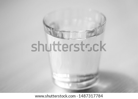glass full of water on the table, selective focus, bw photo #1487317784