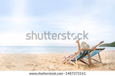 Summer beach vacation, Young asian woman relaxing on beach chair arm up her hand with floppy hat. Background with copy space. Pattaya, Thailand #1487373161