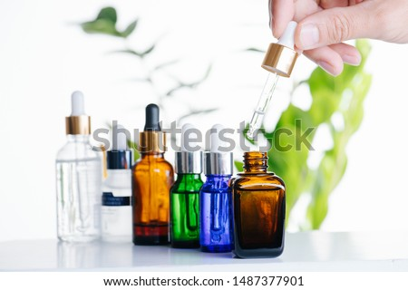 Female hand filling dropper with cosmetic liquid from glass vial over plants on white. Multi-colored vials with pipette plastic caps for essential oils, perfumes and skincare substances in a row. #1487377901