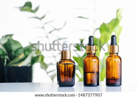 Transparent cosmetic amber glass dropper bottles over green plants on white background. Vials with pipette plastic caps for essential oils, perfumes and skincare substances. Three in a row. #1487377907