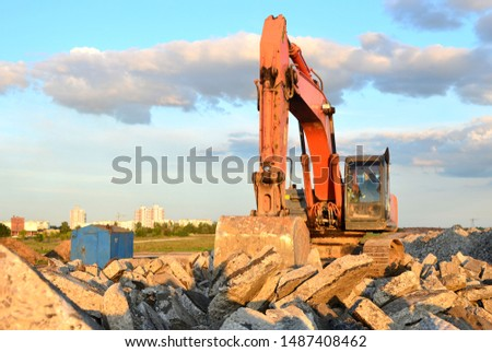 Large tracked excavator digs the ground for the foundation and construction of a new building in the city. Road repair, asphalt replacement, laying or replacement of underground sewer pipes - Image #1487408462