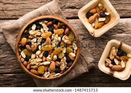 Healthy trail mix snack made of nuts (walnut, almond, peanut) and dried fruits (raisin, sultana) in wooden bowl, photographed overhead (Selective Focus, Focus on the trail mix in the big bowl) #1487415713