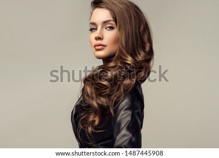 Beautiful stylish woman wearing  black leather jacket. Fashionable and self-confident girl with long curly hair. Clothing, style and fashion #1487445908