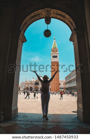 woman in front of bell tower of san marks square at venice italy summer time silhouette