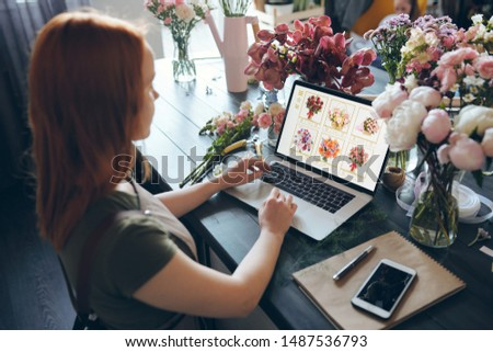 Busy florist standing at wooden counter with fresh flowers and using laptop while finding flowers on internet shop #1487536793