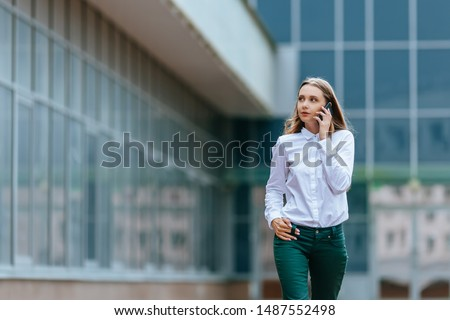 Young famale calling on a smartphone and walking on street. Attractive businesswoman talking by phone. Office building and in the Business District Background. Technology internet and happy people #1487552498