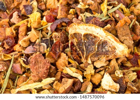 Heap of dried fruit tea infusion with oranges and strawberries mixed with tea leaves and assorted herbs close up macro with selective focus #1487570096