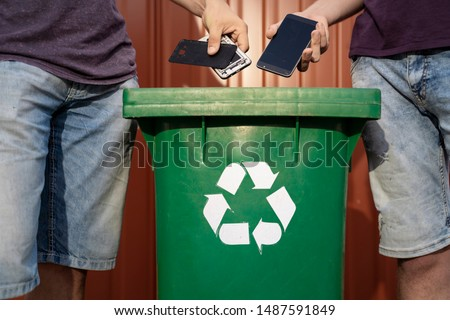 Man throwing phones into recycle bin / obsolete technology, e waste   #1487591849