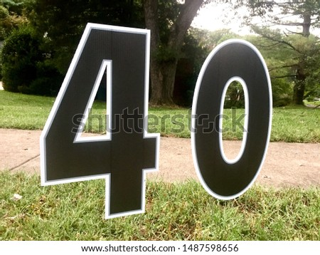 """The number """"40"""" is displayed in a yard marking a 40th birthday party."""