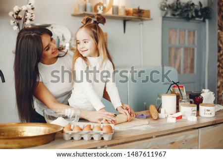 Family in a kitchen. Beautiful mother with little daughter #1487611967