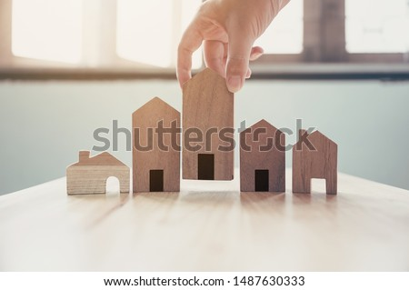 Hand choosing wooden house model, Mortgage and real estate property investment #1487630333