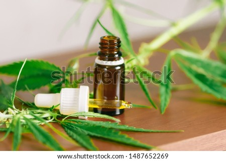 Cannabis plant herbal pharmaceutical CBD oil from jar. Wellness Hemp Cannabidiol. CBD oil bottles cannabis extract tincture liquid on wooden table. Medical marijuana concept. Place for copy space #1487652269