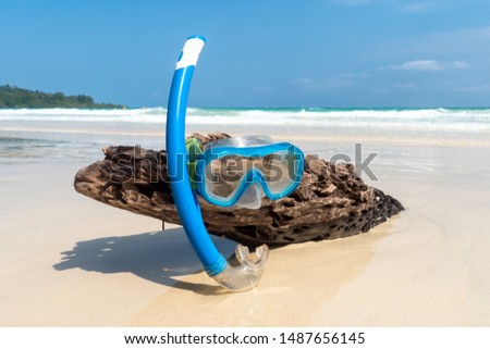 Snorkeling mask on the dry tree wet with beautiful blue sea and island in sunny day of summer. Snorkeling equipment on a wooden log sticking out of the sand. beach with white sand. #1487656145