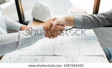 Architect and engineer construction workers shaking hands while working for teamwork and cooperation concept after finish an agreement in the office construction site, success collaboration concept  #1487686430