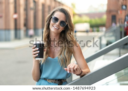 young caucasian girl in blue dress and sunglasses holds cup takeaway coffee. Stands at entrance to office building. #1487694923