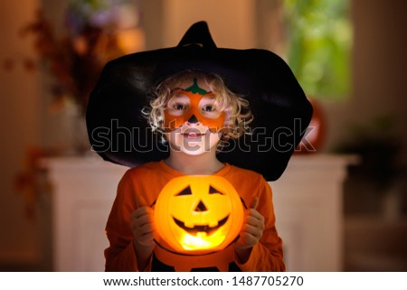 Child in Halloween costume. Kids trick or treat. Little boy with pumpkin face painting and lantern. #1487705270