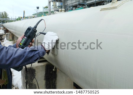 Close up shot of Ultrasonic thickness technician inspector looking at scale on monitor pipe line for using detector gage commencing inspection on wall thickness Royalty-Free Stock Photo #1487750525