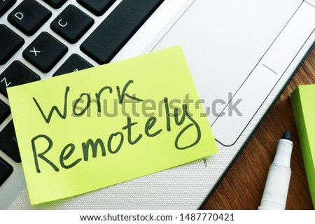 Work Remotely memo stick. Laptop for remote job. Royalty-Free Stock Photo #1487770421
