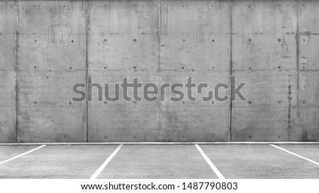 Line of several empty parking lots in an open garage with concrete wall #1487790803