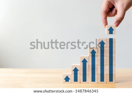 Ladder career path for business growth success process concept.Hand arranging wood block stacking as step stair with arrow up Royalty-Free Stock Photo #1487846345