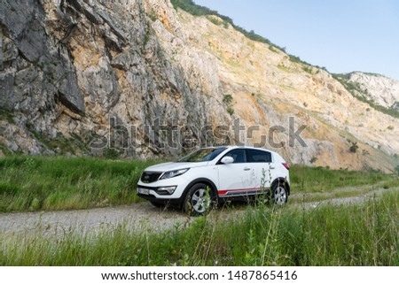 Serbia - 09.21.2018 / car Kia Sportage 2.0 CRDI awd or 4x4, white color, parked on a path that leads to the top of a rocky mountain, with a very steep cliff in the background. #1487865416
