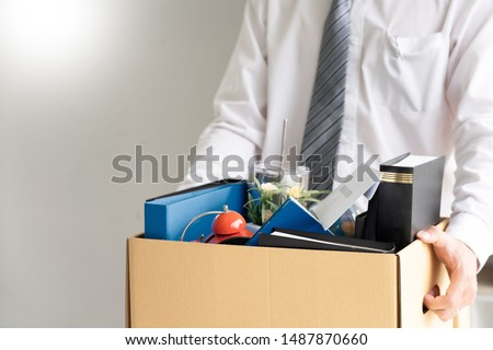 businessman has a brown cardboard box and resignation letter write reason for resigning from work or unemployment and change job concept Royalty-Free Stock Photo #1487870660