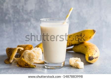 Banana smoothie of organic bananas. There is a high glass filled with banana smoothie in the centre, and bananas and banana peels around the drink. With an environmentally friendly paper straw. #1487883998