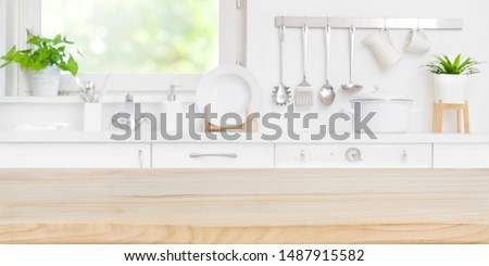 Wooden table top on blur kitchen room and window background #1487915582