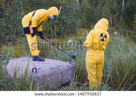 Two dosimetrist  in protective suite and mask with geiger counter measuring radiation level in danger zone #1487930837