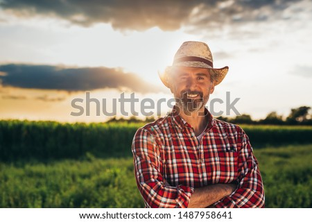 portrait of middle aged bearded man with hat, standing arms crossed and looking at camera, outdoors in meadow #1487958641