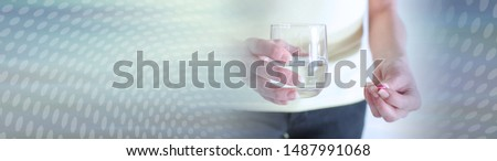 Woman about to take a pill with a glass of water; panoramic banner #1487991068