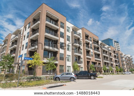 Apartment building with cars on outdoor parking garage in suburbs area of Dallas, Texas, USA. New development multi-Storey flat unit, group housing complex condos for modern living style #1488018443