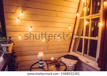 Close up view of nautical theme home balcony at night with string light bulbs. #1488032381