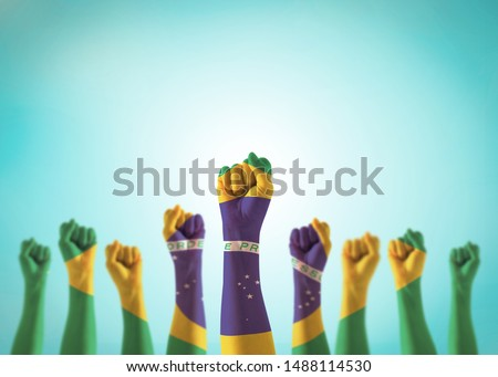 Brazil flag on people hands with clenched fists raising up for labor day national holiday celebration and stay strong for Brazilian power isolated on blue sky background (clipping path) #1488114530